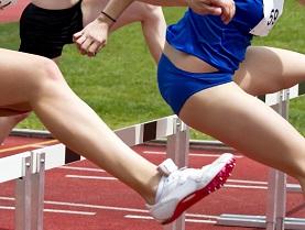 Female sprinter leaping over hurdles
